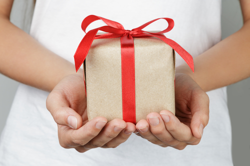 Braut hält Geschenk in der Hand für Bräutigam