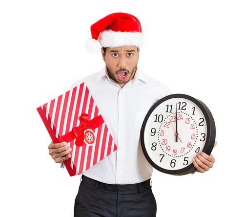 Mann mit Weihnachtsmütze, Geschenk und Uhr in der Hand