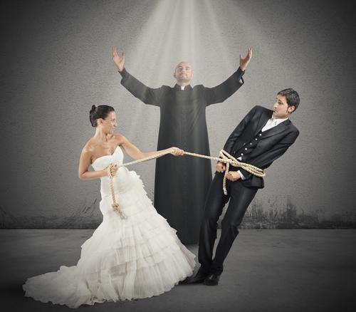 Pfarrer mit Brautpaar, Braut fesselt Bräutigam