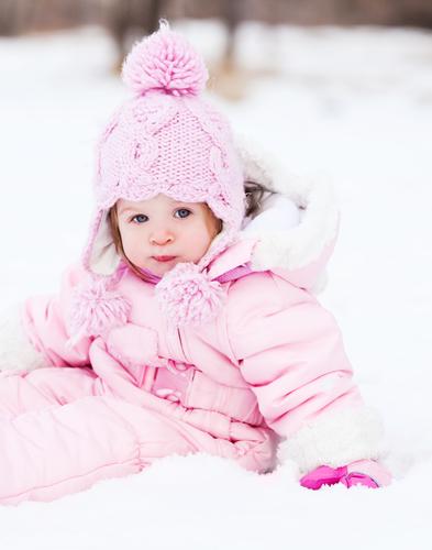 Baby im Schnee mit rosa Winter Outfit