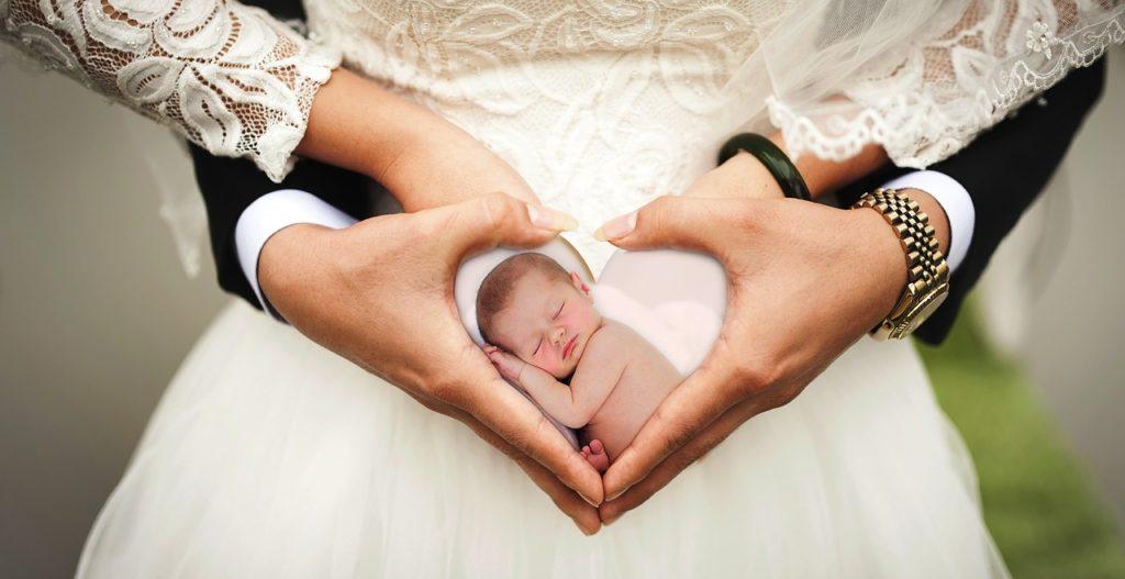 Braut und Bräutigam formen ein Herz mit den Händen am Bauch der Braut. Darin ein Babyfoto.