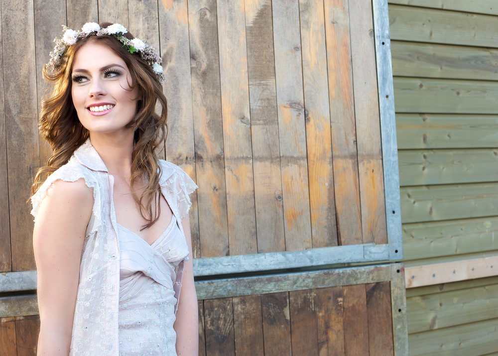 Beautiful young bride with flowers in her hair is smiling and standing next to a barn door